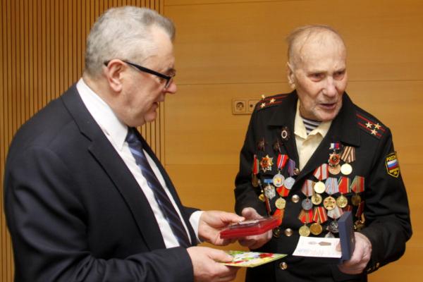 Генконсул РФ Юрий Грибков вручает Александру Михайловичу Разгуляеву юбилейную медаль